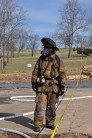 A fire fighter stands in full gear.