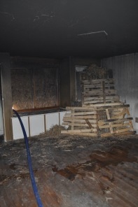 Wood pallets are stacked against the corner of a room that will soon be burned for the fire training.