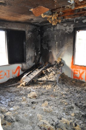 After a burn, smoke and ash stain the upper walls and ceiling of one of the rooms