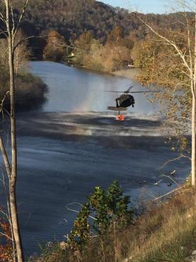 A Kentucky National Guard Blackhawk picks up 600 gallons of water in a Bambi Bucket to drop over the fires in Southeastern Kentucky.