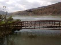 Smoke looms across a lake and bridge.