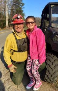 One of the firefighters takes a moment to pose with the girl who held up the thankyou sign.