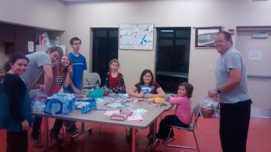 Girlscouts assembling carepackages for firefighters.