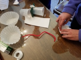 A student packs cotton balls into a coffee cup lid to serve as a filter to collect particulate matter.