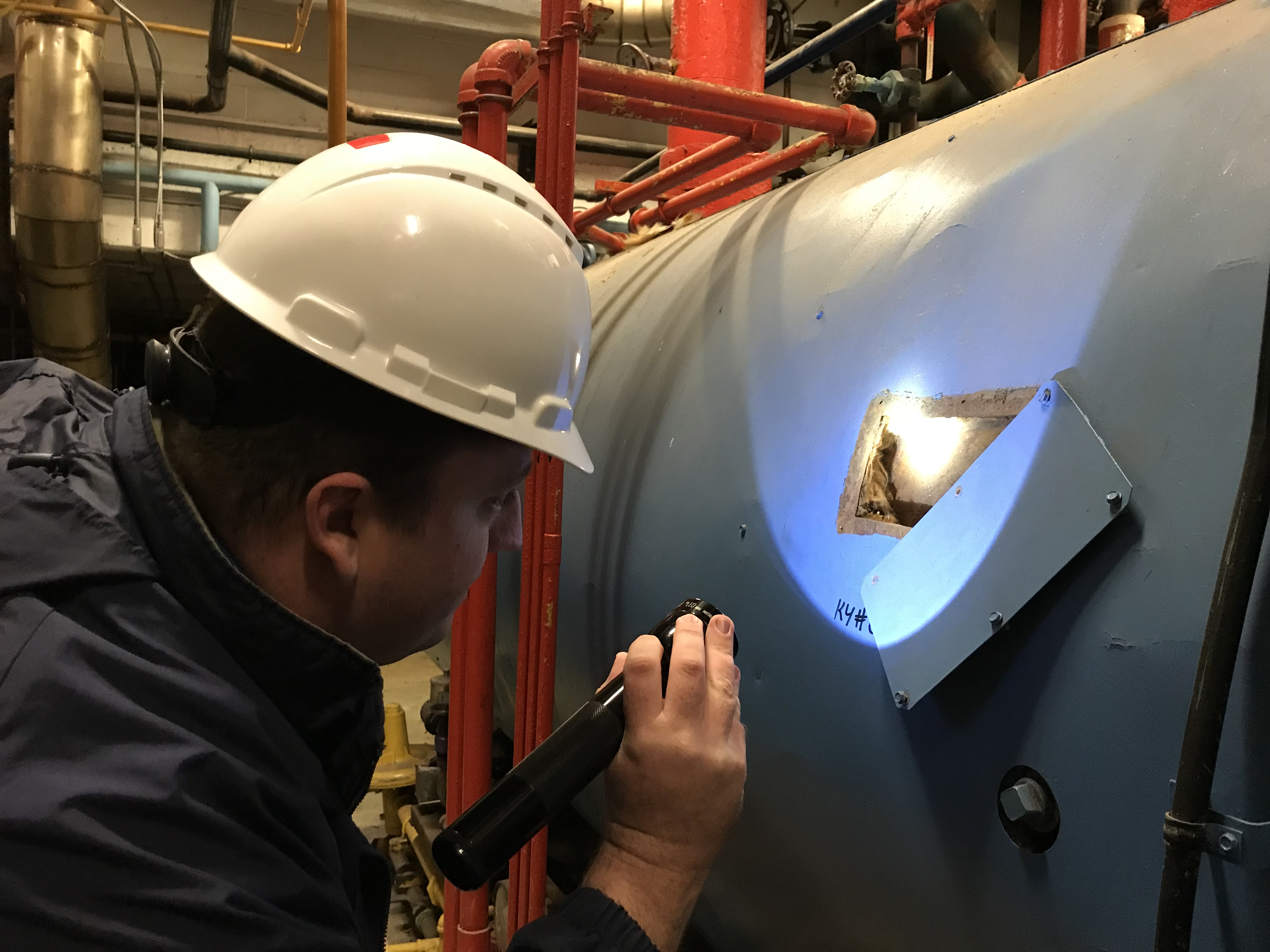 Inspecting boiler insulation. Photo by Roberta Burnes.